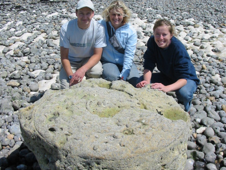 Robert Randell, Denise Randell and Lucinda Shepherd crouched behind a giant Parapuzosia ammonite at Peacehaven